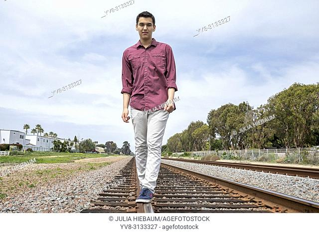 Young man walking on railway tracks