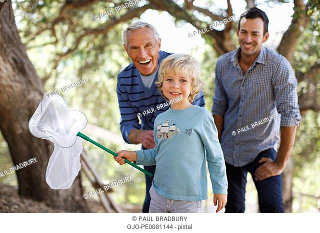 Three generations of men playing with butterfly net