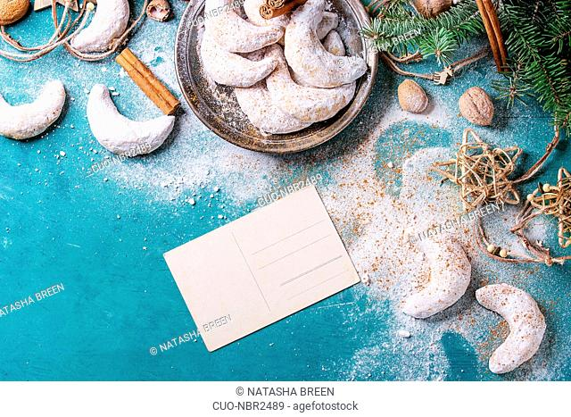 Homemade Christmas nuts cookies crescent with sugar powder in holiday decoration with empty greeting card and fir tree over turquoise wood texture surface with...