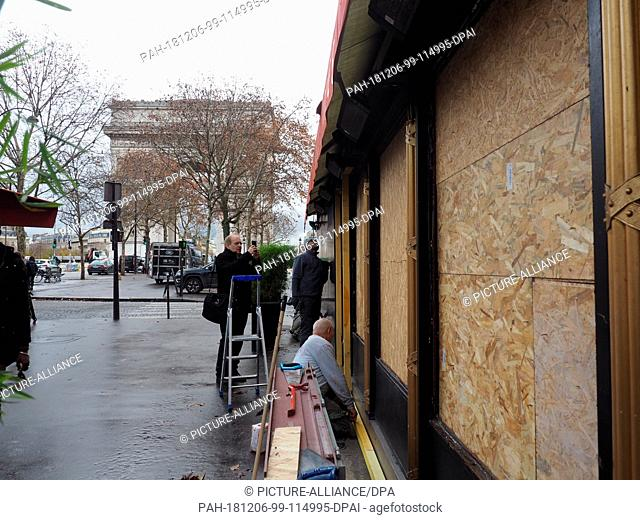 """06 December 2018, France (France), Paris: Workers are securing the terrace of the """"""""La Belle Armée"""""""" restaurant, which was damaged in protests last weekend in..."""
