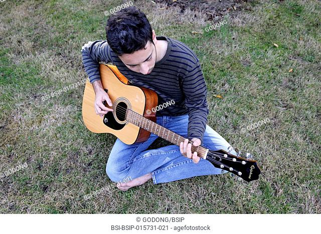 Young man playing a guitar in a garden. France