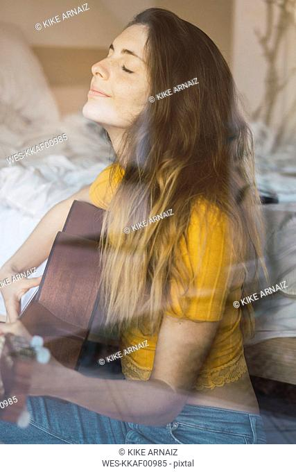 Portrait of content young woman sitting behind windowpane playing guitar