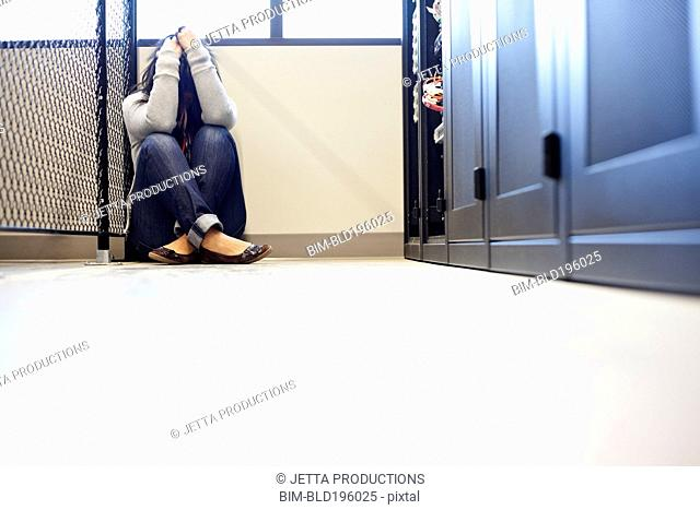 Frustrated Japanese businesswoman sitting on floor of office technology room