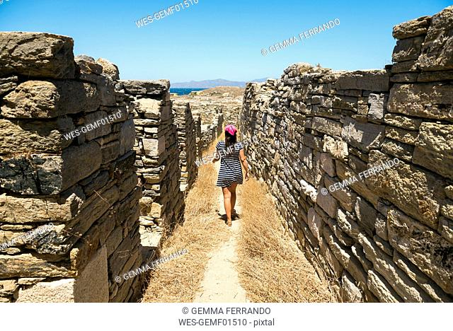 Greece, Mykonos, Delos, woman walking along the old houses at archaeological site