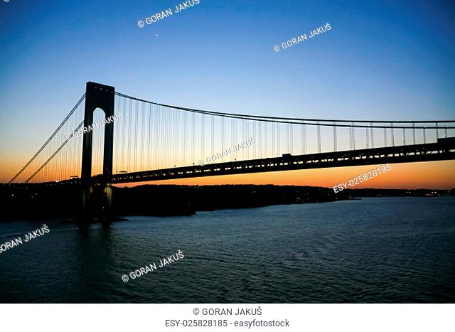 A low angle view of the Verrazano Narrows Bridge in New York at sunset.The Verrazano Narrows Bridge is a double decked suspension bridge that connects Staten...