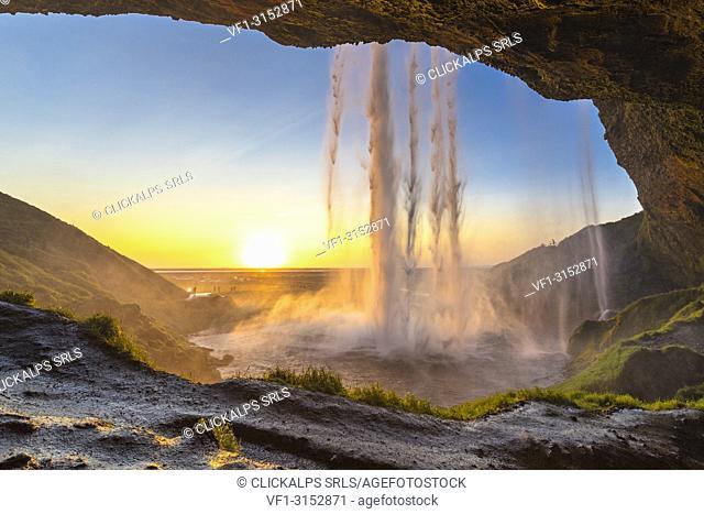 Behind the Seljalandsfoss waterfall at sunset (Skogar, Southern Region, Iceland, Europe)