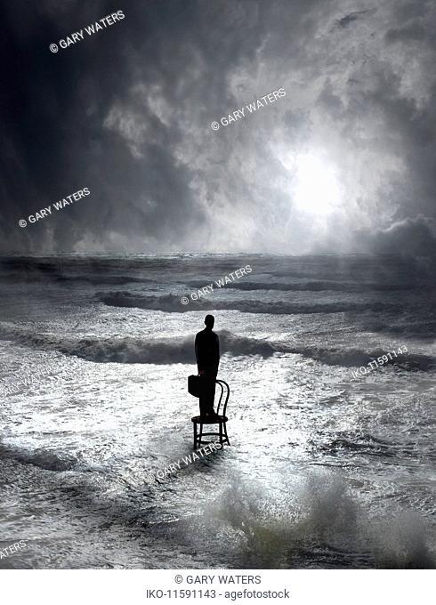 Businessman standing on chair in ocean waves