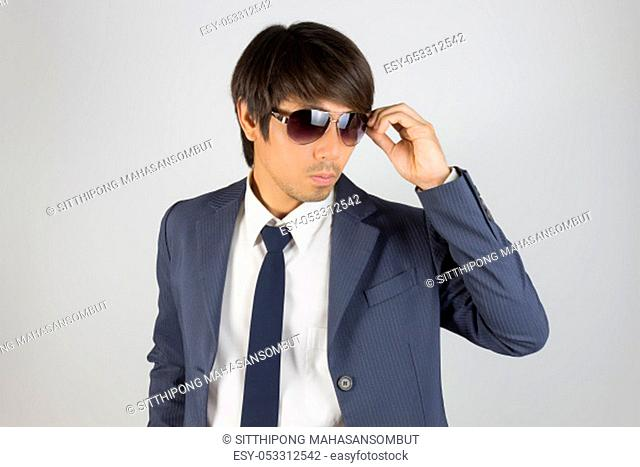 Young Asian Portrait Businessman in Navy Blue Suit Touch Sunglasses and Look Beside on Grey Background