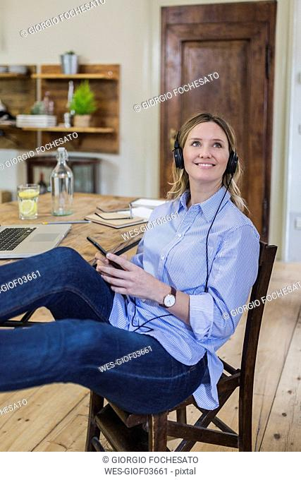 Smiling woman sitting at desk at home with feet up listening to music