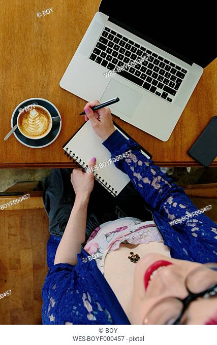 Young woman with laptop and notebook sitting in a coffee shop, top view