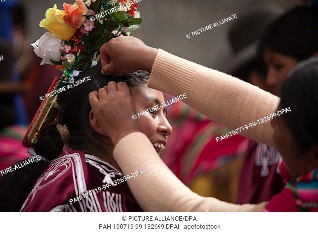 19 July 2019, Bolivia, La Paz: A young woman gets ready for a traditional dance in front of the Supreme Electoral Court. There President Morales presented his...