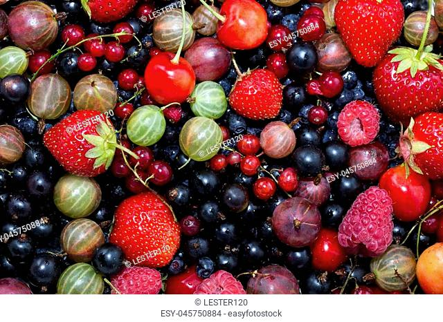 berry background with fresh raspberries, blueberries, currants, strawberries, cherries