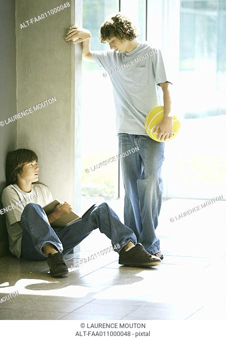Teen boy with basketball approaching second boy studying in hallway