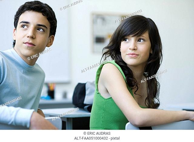High school students in class, looking over shoulders with interest