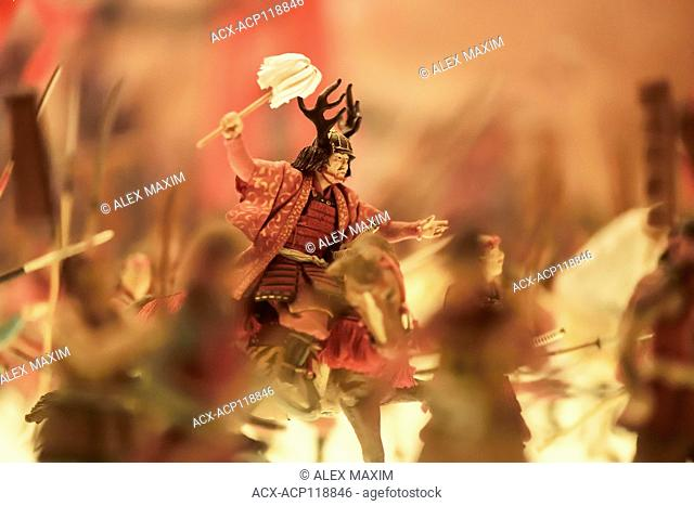 Miniature model of a Japanese samurai warrior riding a horse on battlefield in war action, artistic shallow focus photo of war in Japan