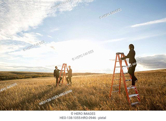 Confident business people climbing ladders on field