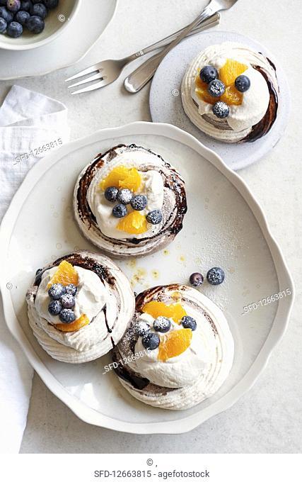 Mini pavlovas with marsala cream, orange and blueberries