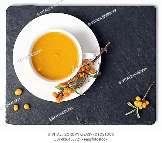 Tea of sea-buckthorn on a black slate stone. A branch of sea-buckthorn. White cup is a top view. Isolated on white background