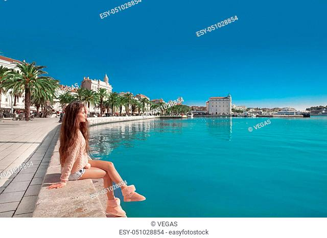 Waterfront of Split, Croatia. Young female traveler with pink backpack enjoying the seafront. Woman looking at view Diocletian palace on famous travel...