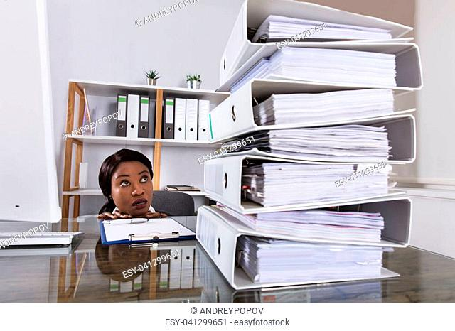 Young African Woman Looking At Stack Of Folders On Desk In Office