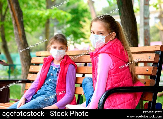 Girls in medical protective masks sit on a bench in the playground