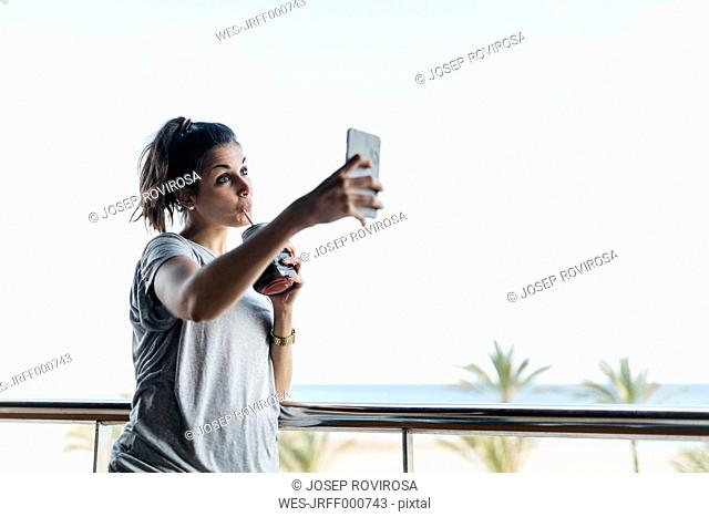 Young woman with healthy drink taking selfie on balcony