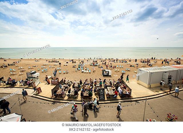 People eating on the beach promenade, Brighton, UK