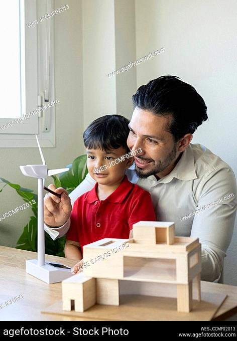 Male architect examining wind turbine model while observed by son at home office
