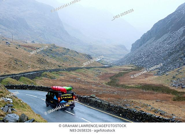 A van with canoes drives on the A4086 road near Pen-Y-Pass in Snowdonia National Park, Gwynedd, Wales, UK