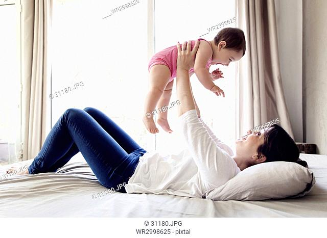 Woman lying on her back on a bed, holding aloft baby girl