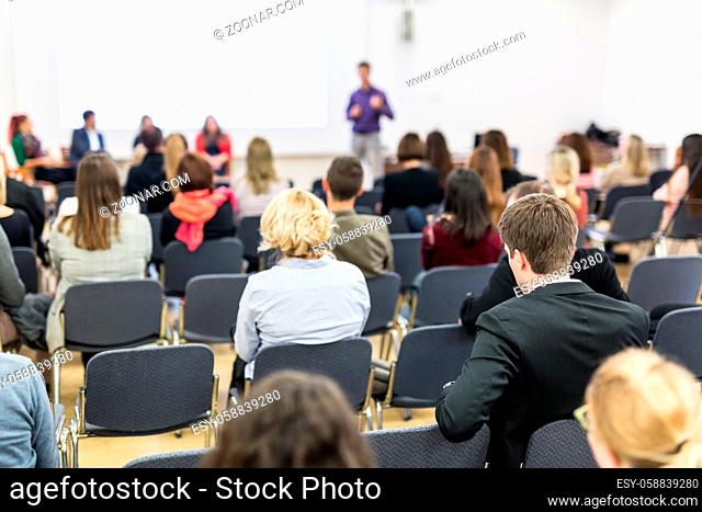 Business and entrepreneurship symposium. Speaker giving a talk at business meeting. Audience in the conference hall. Rear view of unrecognized participant in...