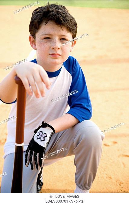 Boy with baseball bat kneeling on ground