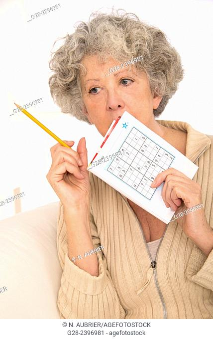 Beautiful senior woman, doing a sudoku game with a pen in her hans and a sudoku magazine, at home