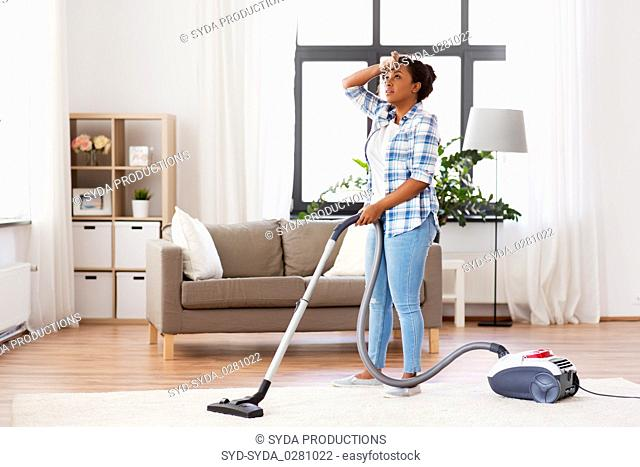 tired african woman with vacuum cleaner at home