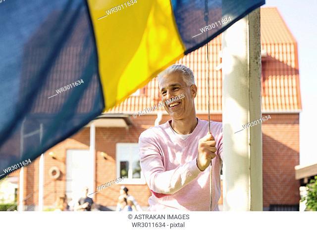 Man raising Swedish flag