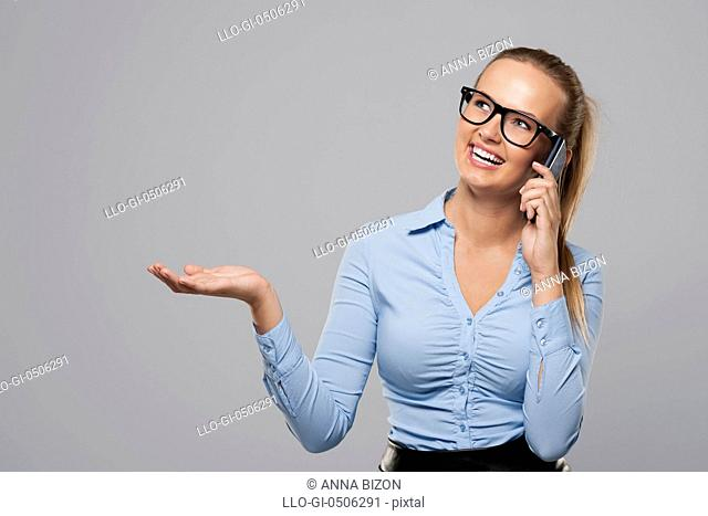 Businesswoman talking on mobile phone and showing on copy space, Debica, Poland