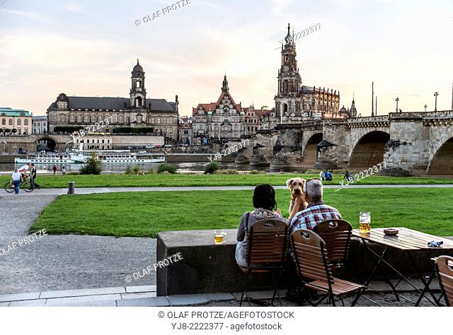 People enjoy sunset in a beer garden in front the Dresden skyline, Saxony, Germany