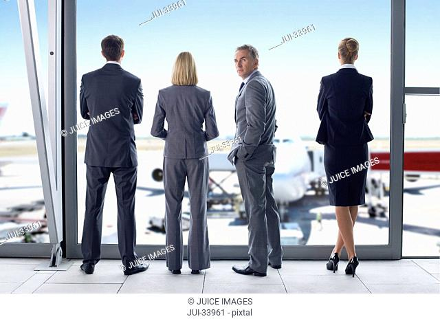 Business people in suits standing at airport window