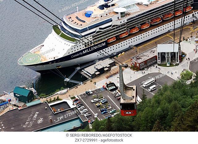 Juneau downtown, city. Alaska. USA. Celebrity Millennium cruise ship docked between snow capped mountains and the Mount Roberts Tramway in Juneau dock, Alaska
