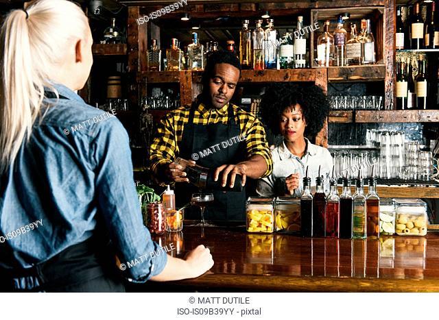 Bartender preparing cocktail in pub