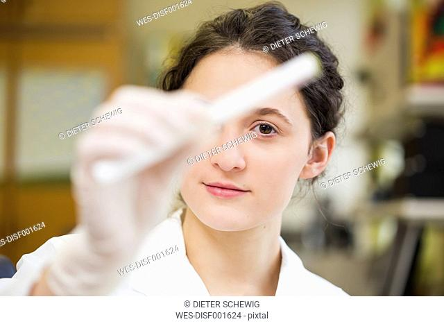 Young lab technician holding medical sample