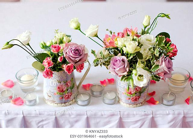 Decoration of flowers in iron vase standing on the table and flat white candles