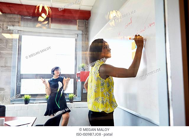 Two women in office, solving problem, using whiteboard, sticky notes stuck on whiteboard