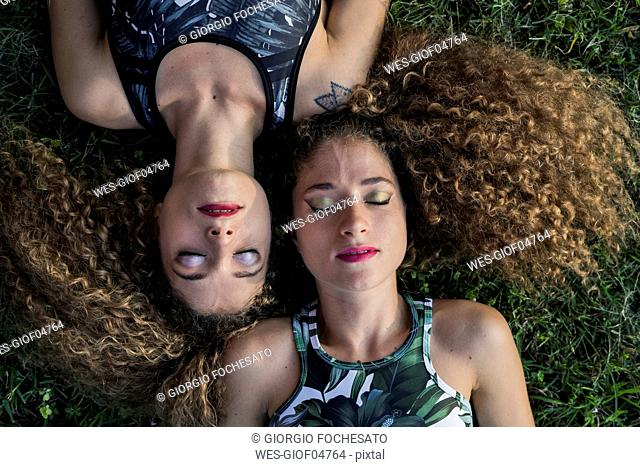 Portrait of rouged twin sisters lying on a meadow, top view