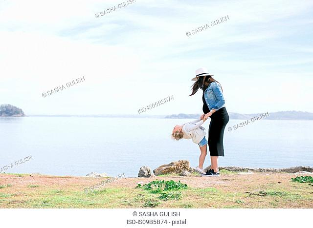 Pregnant mother playing with daughter at coast
