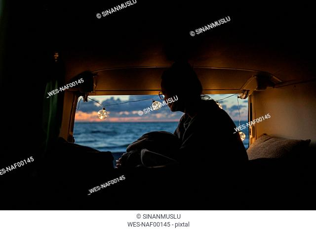 Woman in a van looking sideways at sunset