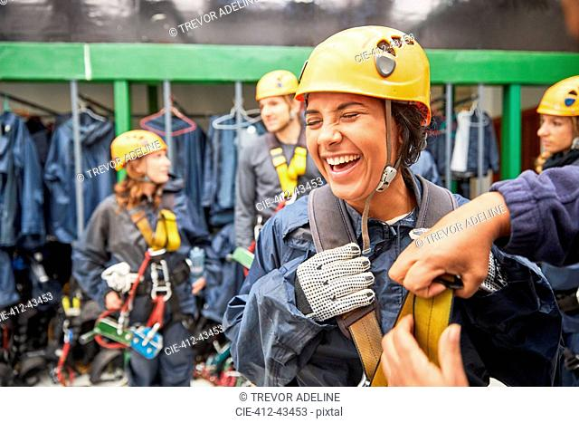 Laughing woman preparing zip line equipment