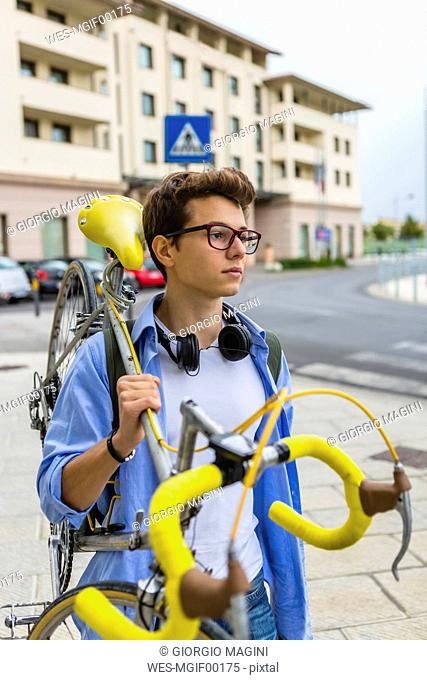Portrait of young man carrying racing cycle on his shoulder