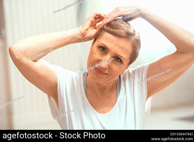 Smiling Mature Woman Gently Stretches Her Neck Touching Her Head. Beautiful Woman Bends Her Head To The Side Pulling It With Hands. Portrait. Yoga