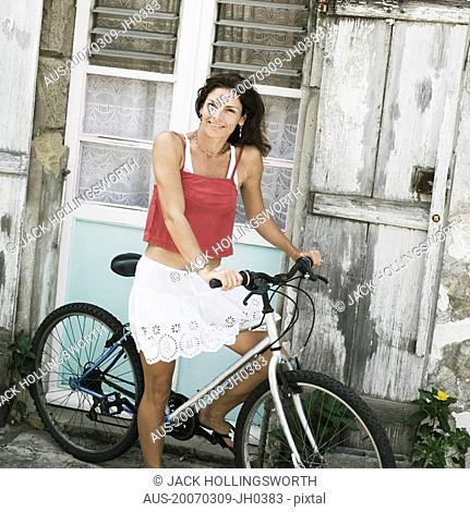 Portrait of a mid adult woman riding a bicycle and smiling